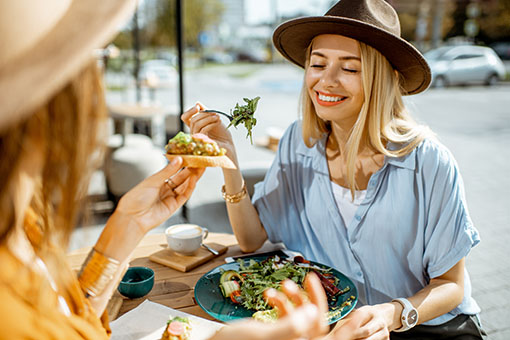 two women enjoy a healthy meal at an outdoor cafe, fat and weight loss hypnosis in Vancouver BC