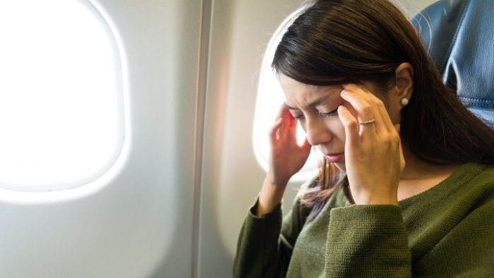 a woman in an airplane, holding her hands on her head, hypnosis for fear and phobias in Vancouver BC