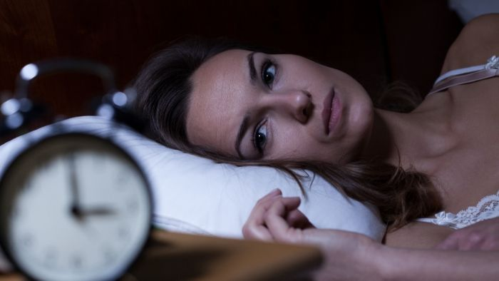 woman laying in bed sleepless, clock shows 3 am, hypnosis for sleep and a restful night