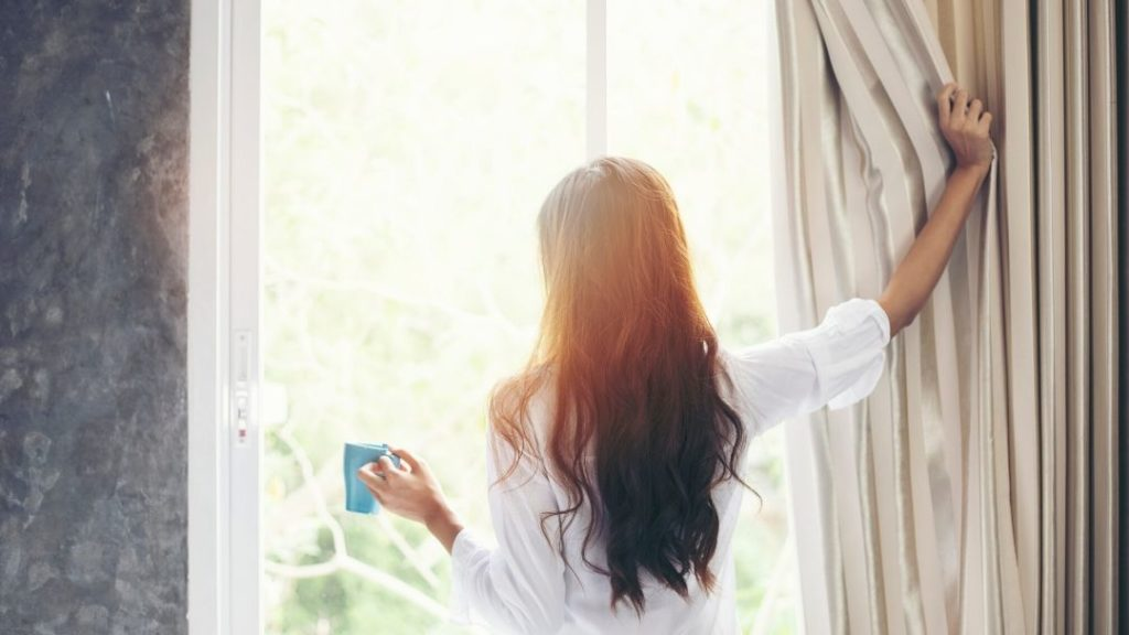 a woman with long brown hair in her white pyjama in front of a window, how to sleep better in 2020