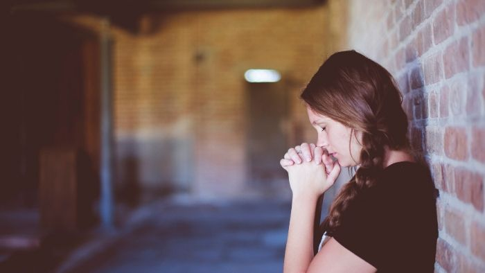 a woman with long brown hair and closed eyes, praying, 5 Signs That You Might Have Anxiety or Anxious Thoughts and Patterns