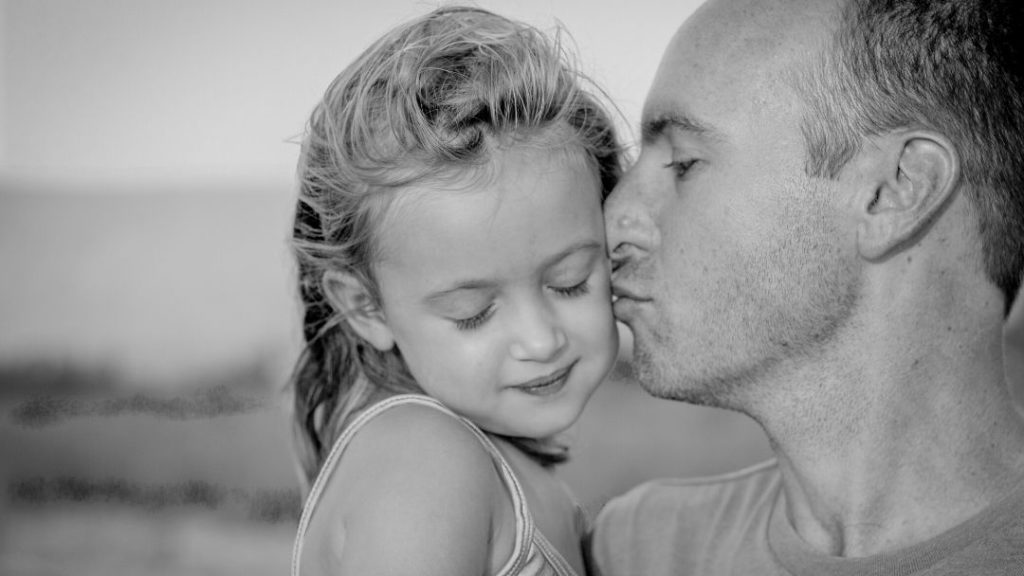 father and daughter on the beach, father kisses daughter on her little face, How to Help Kids and Adults Shift Away from Anxious Thoughts