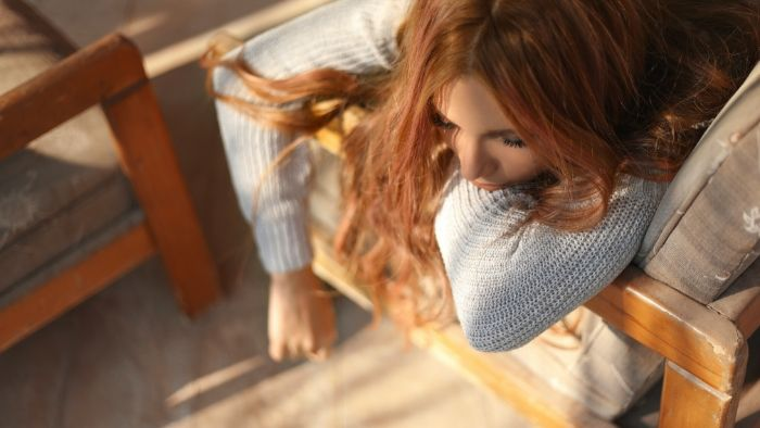 a woman with long red hair and white pullover, laying on her bed, sleepless, Hypnosis for Insomnia in Vancouver, BC