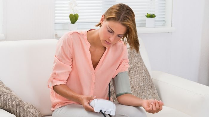 a woman with short brown hair, pink top and white pants is taking her blood pressure, Online Hypnosis for High Blood Pressure in Vancouver, BC