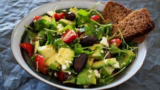 a salad with greens, tomato, and avocado, how to get a better night sleep