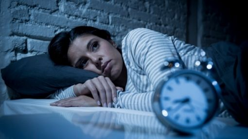 insomniac female lying awake in bed in the middle of the night